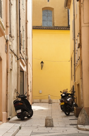 Scooters parked at the old buildings. St. Tropez street and buildigs. photo