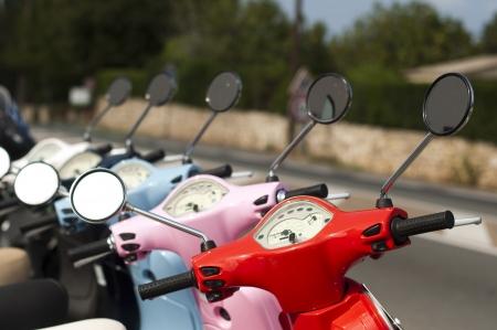Een lijn van bromfietsen  scooters op de stad straat.