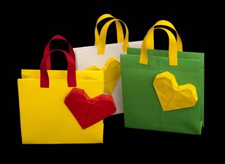 Green, yellow and white shopping bags with heart. Isolated origami photo