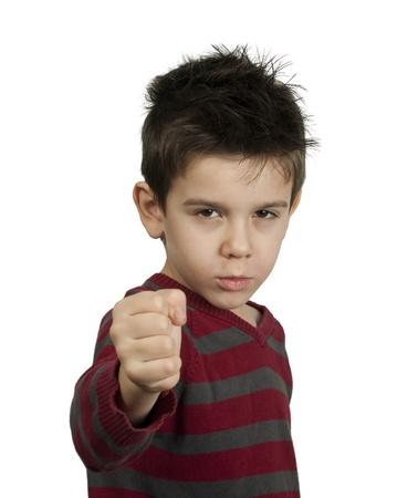 conflictos sociales: Ni�o peque�o que amenaza con un pu�o para luchar contra blanco aislado