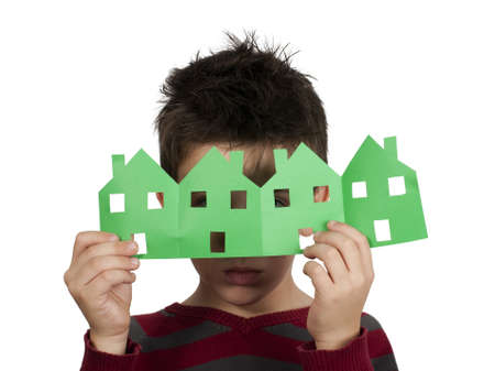 Little boy holding green houses made of paper. White isolated Stock Photo - 16508985