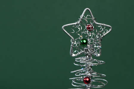 Silver Christmas tree with ornaments. Green Background photo