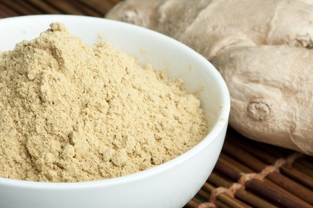Powdered ginger in a bowl and whole ginger on wooden base photo