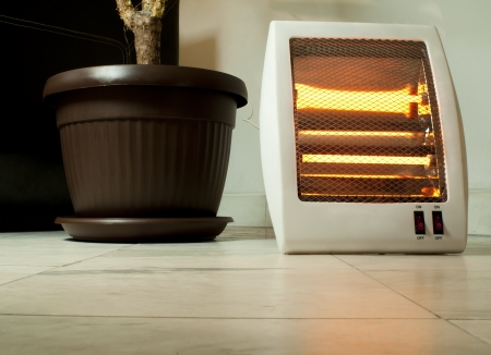 halogen: Electric heater with halogen coils. Flower pot and heater on marble slabs