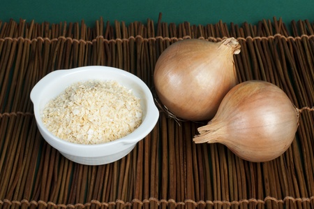 Mature onion and bowl with dried onion powder on wooden base photo