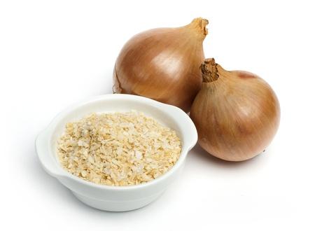 Reife Zwiebeln und Schüssel mit getrockneten Zwiebelpulver weißem