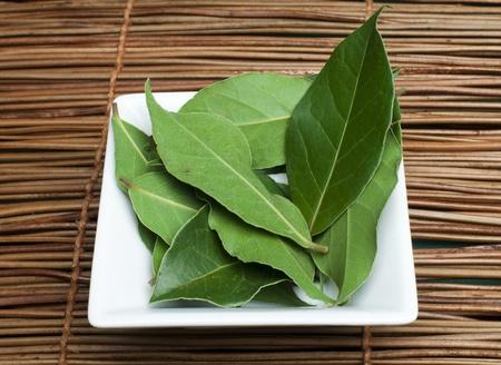 Bay leaf spice in a bowl on wooden base