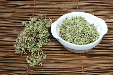 Dried oregano in a bowl on a wooden base photo