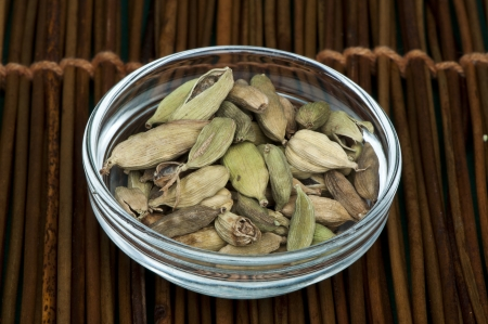 cardamum: Dried cardamon in a bowl on wooden base