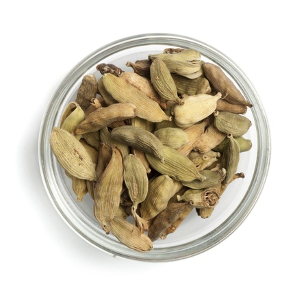 cardamum: Dried cardamon in a bowl on white background
