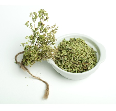 Dried oregano in a bowl and oragano twigs on white background Stock Photo - 16622493