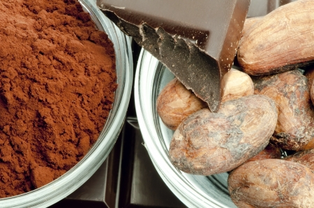 Cocoa beans, cocoa powder in bowls and chocolate bar close up