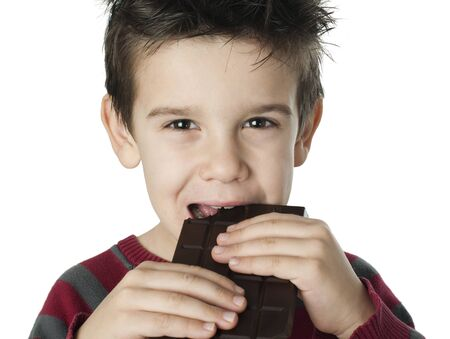 Smiling little boy eating chocolate. White isolated