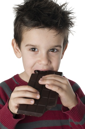 Smiling little boy eating chocolate. White isolated photo