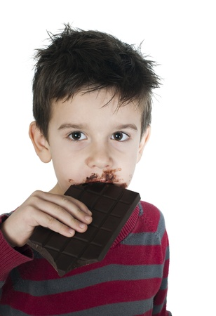 Smiling kid eating chocolate. Smeared stained with chocolate lips. White isolated Stock Photo - 16791379