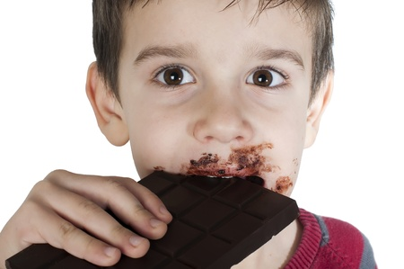 Smiling kid eating chocolate. Smeared stained with chocolate lips. White isolated Stock Photo - 16791314