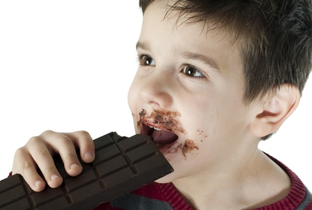 Smiling kid eating chocolate. Smeared stained with chocolate lips. White isolated Stock Photo - 16791434