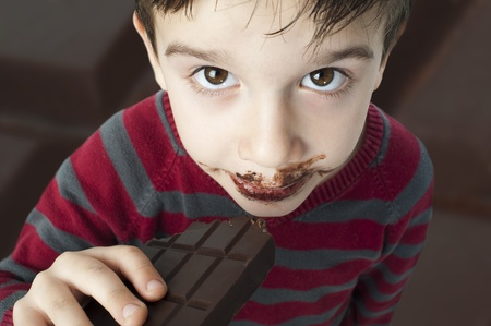 Smiling kid eating chocolate. Smeared stained with chocolate lips.