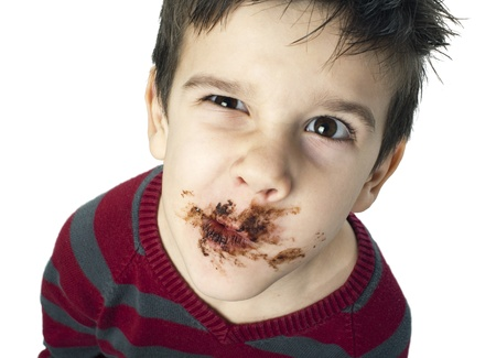 Smiling kid eating chocolate. Smeared stained with chocolate lips. White isolated Stock Photo - 16791329