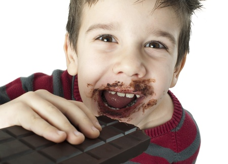 Smiling kid eating chocolate. Smeared stained with chocolate lips. White isolated Stock Photo - 16791326