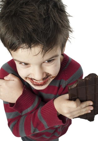 Smiling kid eating chocolate. Smeared stained with chocolate lips. White isolated Stock Photo - 16791452