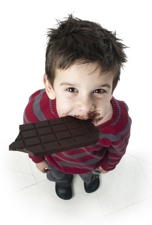 eat smeared: Smiling kid eating chocolate. Smeared stained with chocolate lips. White isolated Stock Photo
