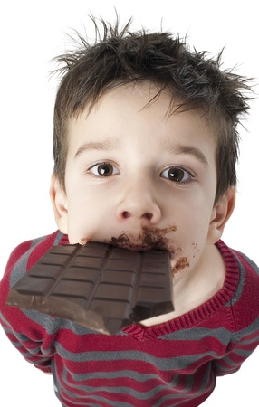 Smiling kid eating chocolate. Smeared stained with chocolate lips. White isolated Stock Photo