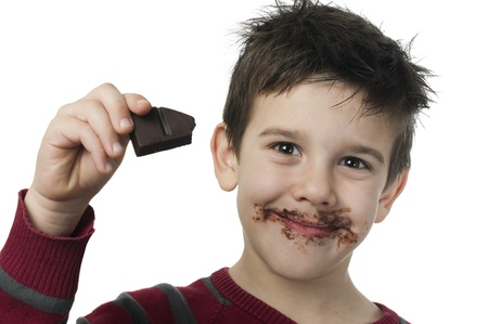 Smiling kid eating chocolate. Smeared stained with chocolate lips. White isolated Stock Photo - 16791330