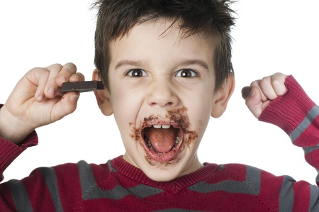 Smiling kid eating chocolate. Smeared stained with chocolate lips. White isolated Stock Photo - 16791643
