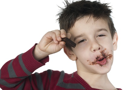 Smiling kid eating chocolate. Smeared stained with chocolate lips. White isolated Stock Photo - 16791381