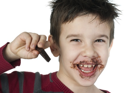 Smiling kid eating chocolate. Smeared stained with chocolate lips. White isolated Stock Photo - 16791375