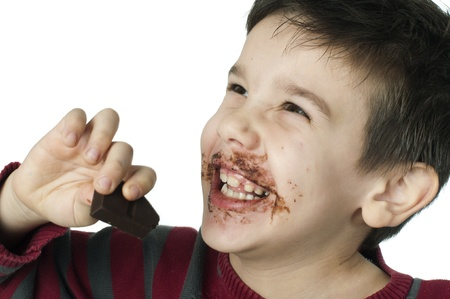 Smiling kid eating chocolate. Smeared stained with chocolate lips. White isolated photo