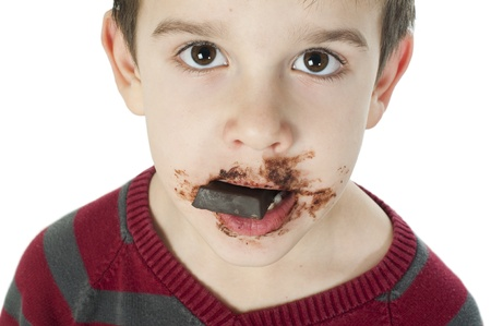 Smiling kid eating chocolate. Smeared stained with chocolate lips. White isolated Stock Photo - 16791437
