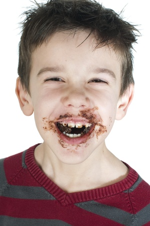 Smiling kid eating chocolate. Smeared stained with chocolate lips. White isolated Stock Photo - 16791659