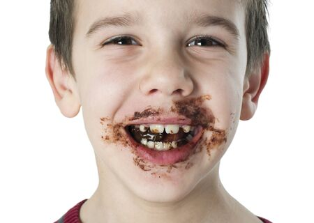 Smiling kid eating chocolate. Smeared stained with chocolate lips. White isolated Stock Photo - 16791368