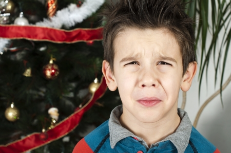 Unhappy little boy on christmass. Christmas tree in the background Stock Photo - 16792352