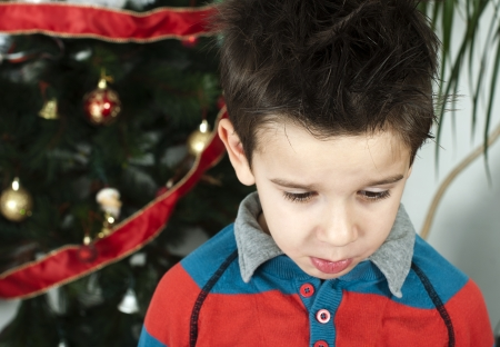 Unhappy little boy on christmass. Christmas tree in the background Stock Photo - 16791656