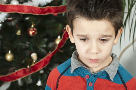 Unhappy little boy on christmass. Christmas tree in the background Stock Photo - 16792368