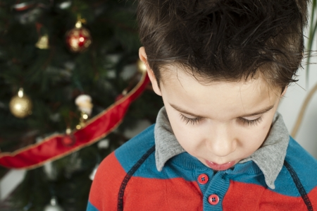 Unhappy little boy on christmass. Christmas tree in the background Stock Photo - 16791640