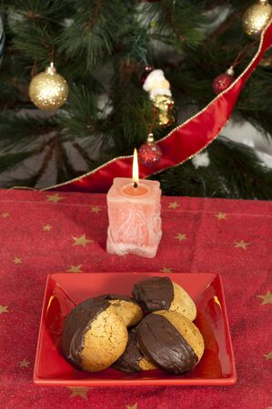 Christmas sweets and candle on the table in front of Christmas tree photo