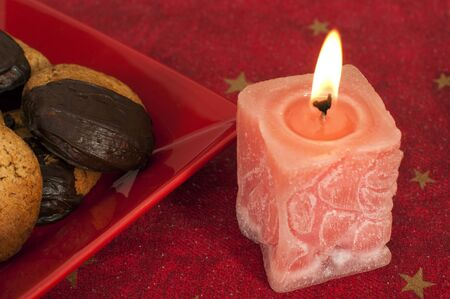 Christmas sweets and candle on the table photo