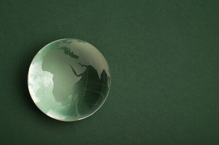 Glass globe on green background photo