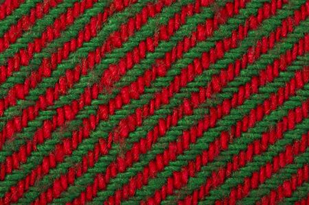 christmas motive: Handmade knit green and red background. Close up structure of the yarn. Christmas colors