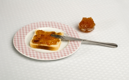 Spread jam on bread with knife. Pink checkered plate photo