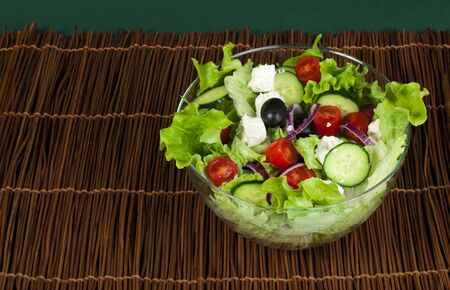 Mixed salad in a glass bowl on a wooden base photo