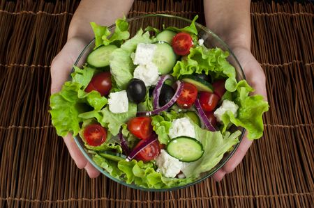Hands holding mixed salad in a glass bowl  photo