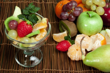 Fruit salad in a glass bowl and fruits  photo