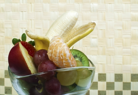 Fruit salad in a glass bowl on wooden base photo