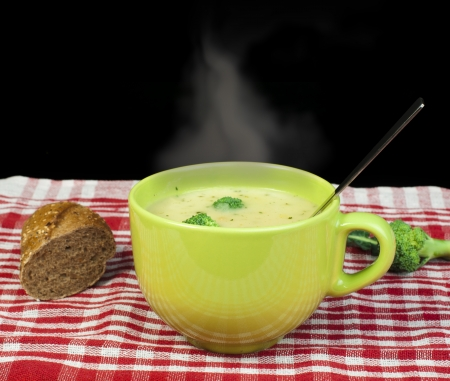 Green Cream broccoli steaming soup Vegetables around the bowl photo