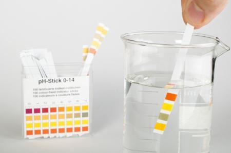 Litmus strips voor het meten van acidity.Beaker met water Stockfoto